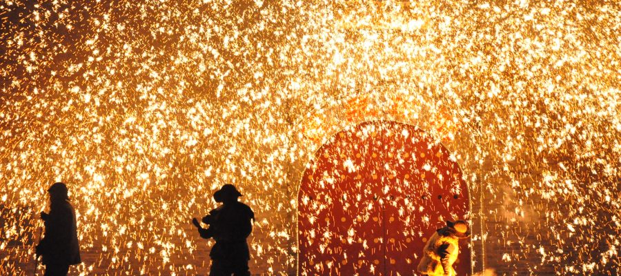 A man in Yu County, China throws molten iron against a wall to mark the ending of the spring festival. The yellow-hot iron explodes when it touches the freezing wall creating a shower of sparks. Shot February 16.